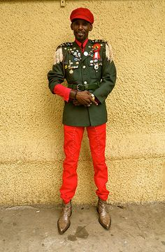 Big Picture - Africa: Man dressed in red trousers and army wear in front of yellow wall African States, Red Trousers, Pictures Of The Week, Sierra Leone, African Fashion, Canada Goose Jackets, Men Dress, Army, Winter Jackets