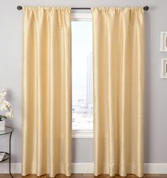 Faux silk drapery panels in a yellowish hue to add a little sunshine inside, while still providing privacy.