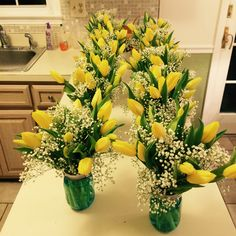 Blue mason jars with yellow tulips and baby's breath make the perfect centerpiece for a spring bridal shower.