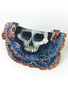 Orange Plaid Skull Hip Bag by Modesty  Hang this unique hand-painted skull on your belt loop or attached a strap for a hands free carrying piece of art. Secures using black velcro and inside has one pocket.  One the side is a buttoned loop to attach that lucky rabbits foot. The overall design consist of a beautiful black floral print and has distress details.   I also take custom orders.