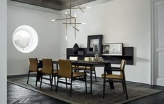 Howard table, structure in black elm and mat emperador marble top. Ipanema chairs in the versions with and without armrest, black elm structure, Quid composition with wall panelling in black elm.