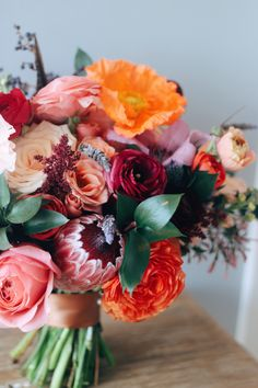 Bright, playful bouquet comprised of bright ranunculus, poppies, protea, and garden roses | Whim Florals