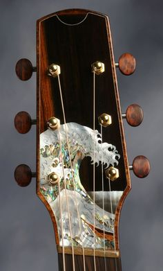 Jimmi Wingert inlay on a Michael Bashkin headstock. Note that is is a fanned-fret instrument.