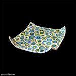 Square ceramic candle pad painted in blue, green and yellow circles and spots with cream background. Kwadratowa ceramiczna podkładka pod świece malowana w niebiesko zielone koła i kropki na kremowym tle.
