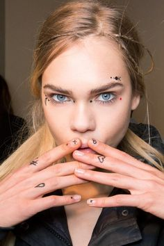 Giamba forecasts this year's music festival makeup with quirky face tattoos and ultrathin braids: