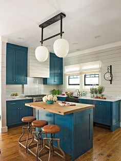 Bold blue cabinets, ship lap walls and range hood
