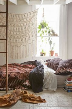 Bed on floor with bohemian decor and books.