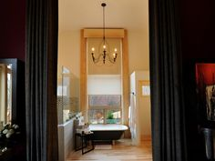 Old World elegance gets a contemporary twist in this master bathroom from the HGTV Dream Home 2011. A dramatic view can be enjoyed as one peers through the master bathroom's 5-foot-wide by 12-foot-tall column of glass. The metal chandelier over the bathtub creates a stunning focal point.  A Lutron shade, concealed during daylight hours in a custom-constructed spruce pine valance box, can be lowered as privacy demands.