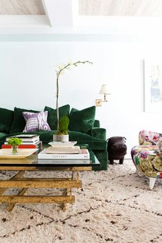 Green velvet sofa with purple pillow, coffee table with books, and floral chair (Bottle Green Couch) Home Living Room, Interior, Emerald Green Sofa, Decorating Rules, Home Decor, House Interior, Green Velvet Sofa, Inspiring Spaces, Interior Design