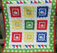 """'Counting Sheep' Perfect for bedtime, this cheerful child's quilt is scattered with adorable little sheep in bright primary colours. It is quilted with waves and backed with red , yellow and blue squares. This would make a great playmat or cot quilt. Size: 41"""" x 41"""""""