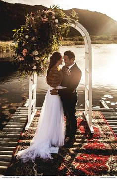 Lakeside opulent wedding ceremony with a beautiful soft wedding dress, dramatic red carpet and black grooms suit! https://www.theprettyblog.com/wedding/a-truly-golden-day/