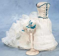 "Lady Doll Undergarments Comprising pique white corset with blue edging and blue lacing holes,two-piece petticoat set with extended train and lace-edged ruffle detail,and a muslin coiffe with tatting trim and blue velvet ribbons. For lady doll about 16"". Presale Estimate: 300/400 Fits and Starts Costumes 