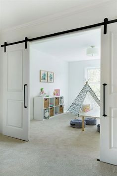 Flex room playroom with barn doors. The landing area opens to a flex room, currently used as a pl . What To Put In A Flex Room Barn Style Sliding Doors, Interior Sliding Barn Doors, Playroom Design, Modern Playroom, Playroom Ideas, Playroom Storage, Living Room Playroom, Playroom Slide, Basement Play Area