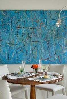 Decoração de apartamento com varada e ambientes integrados e a paleta de cores inspirada na natureza local. Na sala de jantar, mesa de madeira, cadeiras brancas, obras de arte, quadro, pintura e luz natural.