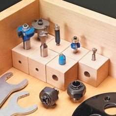 "Make wooden cubes out of 1-1/2"" stock and drill 1/4"" and 1/2"" holes in each cube to fit various bits in for storage."