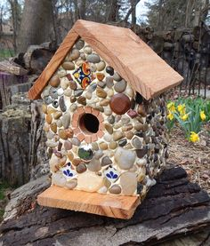 """Hacienda birdhouse for sale... available at http://www.stonedbirdhouse.com/   Stones and river rock collected from the shores of Lake Michigan, local rivers and from creek beds. Embellished with pieces of hand painted Mexican tile, buttons and  knob for the perch. Roof and base stained medium walnut. Suitable for outdoor or indoor décor.   7 1/2"""" wide X 10"""" high X 8"""" deep    1 1/4"""" opening"""