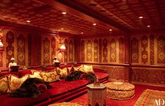 Evoking a pasha's luxurious retreat, the screening room boasts custom-made banquettes and ottomans, Fendi fur throws, and printed linen panels by Iksel Decorative Arts on the ceiling and walls.