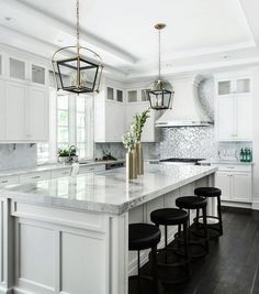 Backless black leather counter stools are positioned on dark stained wood floors in front of a white island topped with a gray and white quartzite countertop lit by Hudson Valley Lighting Hollis Lanterns as a white French hood mounted on silver mosaic metallic backsplash tiles over a stainless steel oven range fixed between white shaker cabinets adorning with polished nickel hardware and a gray and white quartzite countertop.