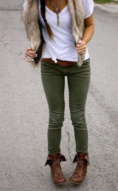 Simple white tee with a faux fur vest over olive skinny jeans and brown ankle boots.