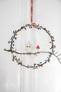 Owl wreath. Rie Elise Larsen metal ring, adorned with buttons, glass ornaments and a small owl on a stick.
