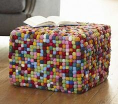 OMG, how super cute. Got an old foot stool? Cover it in puffballs.