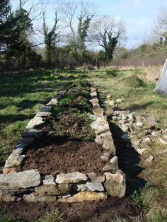 stone-bordered raised bed with gopher wire underlayment-- nice
