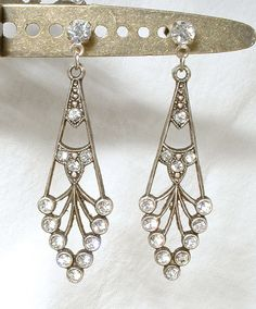 Offering an EXQUISITE pair of Art Deco flapper antiqued silver clear crystal rhinestone dangle earrings. These were made from vintage old stock classic Art Deco designed findings that have an antiqued silver finish and are adorned with brilliantly clear sparkly pave set crystal rhinestones. Photos dont even come close to capturing the sparkle! The drops have been hung from new silver plated rhinestone studs for pierced ears that Ive slightly antiqued. Earrings hang down 1 7/8 inches. I r...