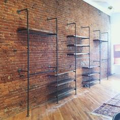 Shelving in front of an exposed brick wall adds a sophisticated touch to any storage area! Looking to add brick to your home? Get started with www. Store Fixtures, Wall Fixtures, Retail Fixtures, Wall Mounted Wood Shelves, Pipe Shelves, Wood Wall, Brick Shelves, Timber Shelves, Floating Shelves