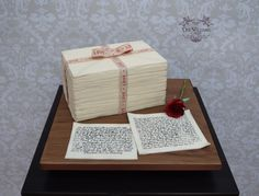A stack of old love letters and notes tied up with ribbon, with a red rose and love notes on a fondant wood effect board. I used my evil cake genius stencils again, they are fab!
