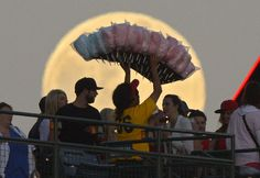 A cotton candy vendor walks in front of the moon during the Los Angeles Angels' baseball game against the Pittsburgh Pirates, on June 22, 2013, in Anaheim, California,
