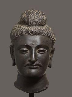 LARGE HEAD OF BUDDHA GAUTAMA Catalog Number: AK1116-194 Black shist India, Gandhara ca. 3rd to 4th century PEDESTAL HEIGHT 24,5 CM, HEIGHT (WITHOUT PEDESTAL) 32,4 CM