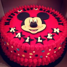 Mickey Mouse Birthday Cake for a Mickey Mouse Birthday Party. Vanilla sponge filled with jam and vanilla buttercream. Covered in deep red vanilla frosting and handmade Mickey Mouse themed cake toppers.