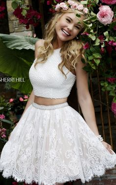 Create an unforgettable scene in Sherri Hill 32313. This two-piece cocktail dress offers a halter neckline with cut in shoulders. The crop top is completely accented with color-coordinating beads adding texture to your sassy vibe. Laced skirt with scalloped hemline perfectly matched the top, giving the dress a vintage yet chic appeal.