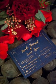 Red floral with deep navy and gold accents! All set atop a wood background. Who said you can't have a rustic wedding with a bit of glam! Vision created by Banana and Bean Events.