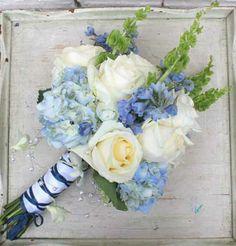 blues. whites,  greens featuring light blue delphinium, light blue hydrangea, white roses,  bells of Ireland.