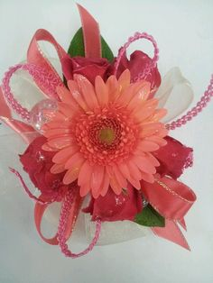Hot pink and coral wrist corsage.  I don't recommend gerbera daisies.  They wilt quickly and are fragile.   Checking on color for your date.