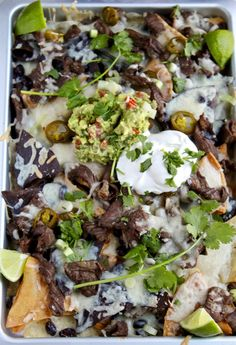 Loaded Steak Nachos. A Tex-Mex favorite, these steak nachos are loaded with seasoned steak, beans, jalapeños, lots of cheese, guac, sour cream and salsa.