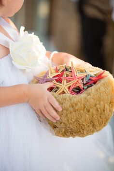 For a beach wedding, this little flower girl tossed colored starfish in lieu of flowers.