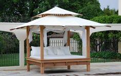 Überdachtes Outdoor Bett mit weißen Vorhängen