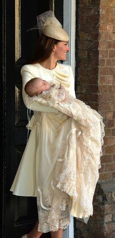 23 October 2013: Prince George's Christening. Duchess wearing an ivory Alexander McQueen leaf crepe jacket with wave ruffle panel, jacket has rounded padded shoulders and silk lining. Georgie Hat by Jane Taylor Millinery, sinamay beret with delicate silk/organza rose and classic veiling trim. Kiki McDonough citrine drop earrings. Russell and Bromley Park Ave platform pumps in beige patent leather.