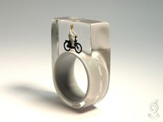 Wheel of fortune – funny bicyclist ring with a mini-bicyclist and her bike on a gray ring made of resin  ///// © Isabell Kiefhaber www.geschmeideunterteck.de
