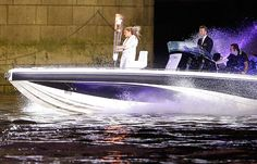 Becks Bond?  -  David Beckham passes under Tower Bridge driving a speedboat named 'Max Power' which carries the Olympic Torch with its torchbearer.