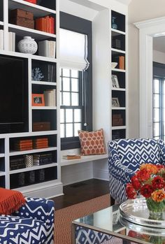 Blue and orange living room features a mirrored waterfall cocktail table and a pair of blue geometric accent chairs lined with orange velvet pillows placed before floor to ceiling built in media unit, with backs of shelves painted blue, filled with a flatscreen TV and orange accents placed next to a floating window seat under a blue framed window.