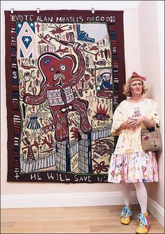 Grayson Perry, dressed as Claire, his female alter ego, beside his needlepoint Vote Alan Measles for God.