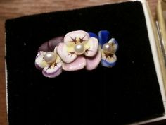 This piece is from the early 1900s. It consists of 3 delicate enameled pansies with a pearl in each center. Each petal was painstakingly applied and enameled. As you can see, there is wear to the enamel on the edges and a chip on the purple pansy, but overall good condition for a piece over 100 years old. It looks like it was marked for gold content and possibly a signature inside the band but both are worn away. It was most likely made by Larter ad Sons. The mounting is 14kt. yellow gold…