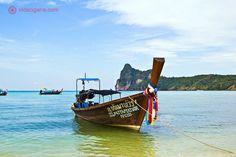Barco estilo longtail, ancorado em praia nas ilhas Phi Phi, na Tailândia e decorado com fitas coloridas, formando uma das imagens icônicas desta região do país.