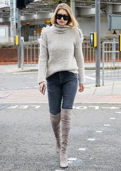 Gigi Hadid in gray jeans, tan Stuart Weitzman boots, and a tan sweater.