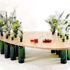 wood tabletop on empty wine bottles to hold flowers or candles. this would be nice on a patio