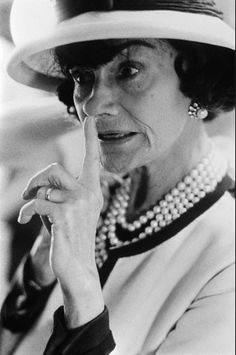 Candid portrait of fashion designer Coco Chanel touching her nose. August 1, 1962