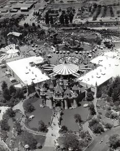 Aerial view of Fantasyland from late 1950's. Note the houses, dirt roads, and such behind the park boundary, the cement pond for the Pirate Ship, and  open grass beyond Fantasyland and the castle towards front of the photo.